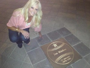 Natalie Niekro kneels next to her Dad's star on the Walk of Fame